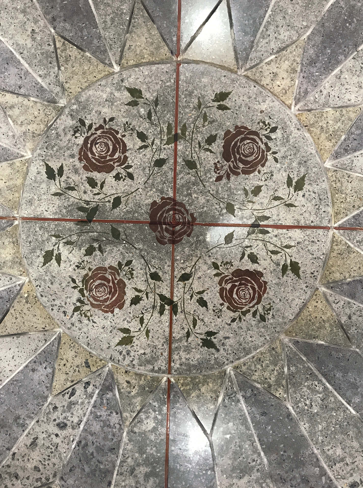 The roses and greenery in the center of the saw-cut showroom floor are made with Flattoo stencils from Surface Gel Tek. Stencils only comprise about 10% of the floor's design.