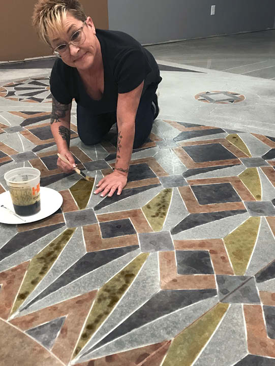 Lee Ann Harris works on the intricate floor using stain and brushes.