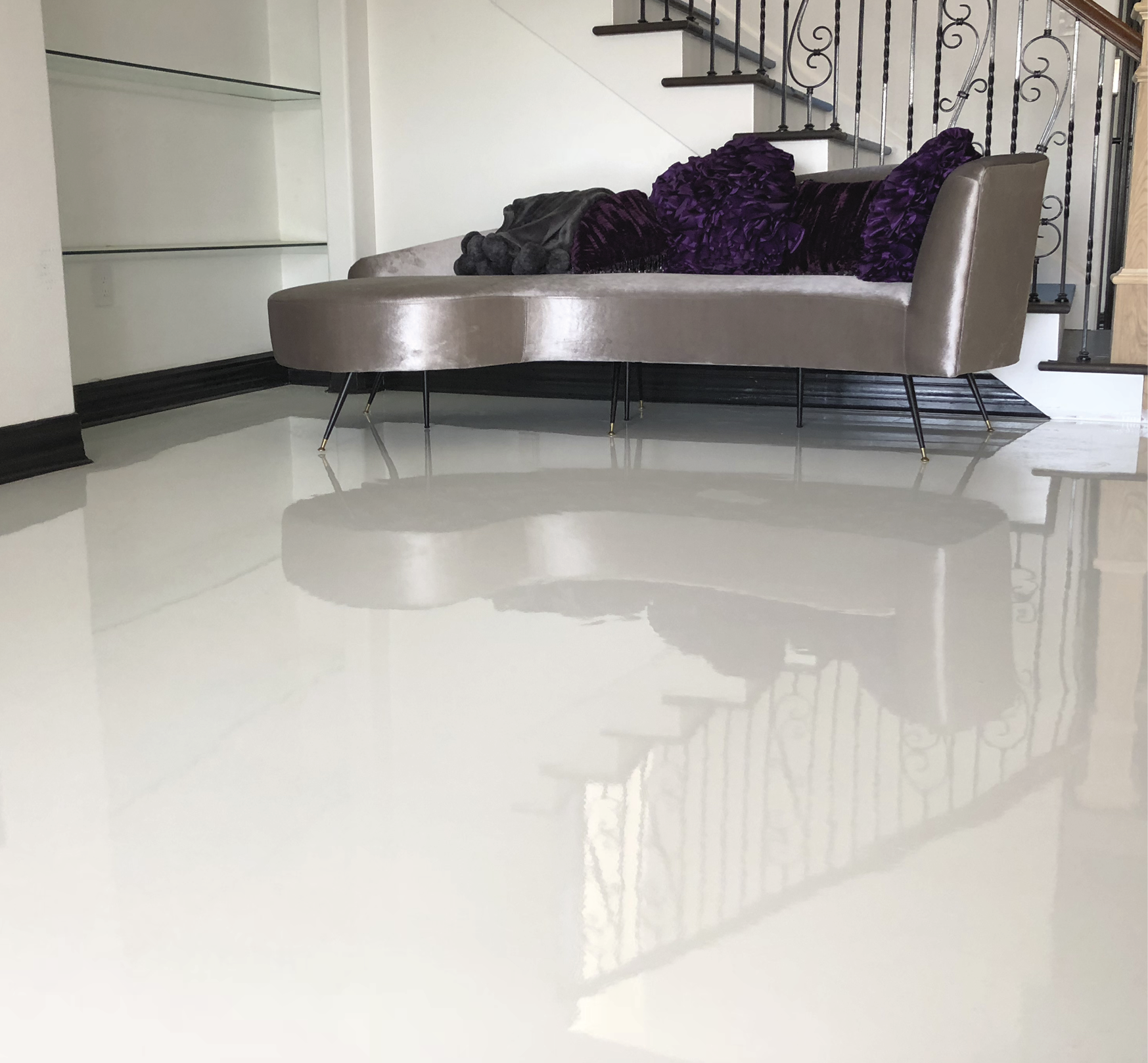 A clean white epoxy floor that is flanked with a white chaise lounge.