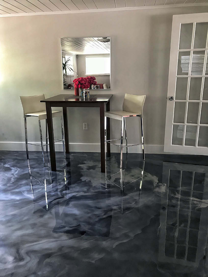 A tall table with tall chairs sit atop an epoxy floor. Colors dark blue and light gray create a swirl that looks like the ocean.