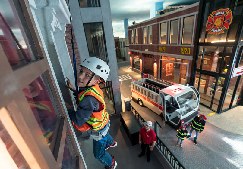 A kid at KidZania experiences what it is like to be a construction worker on a mini version of a city.