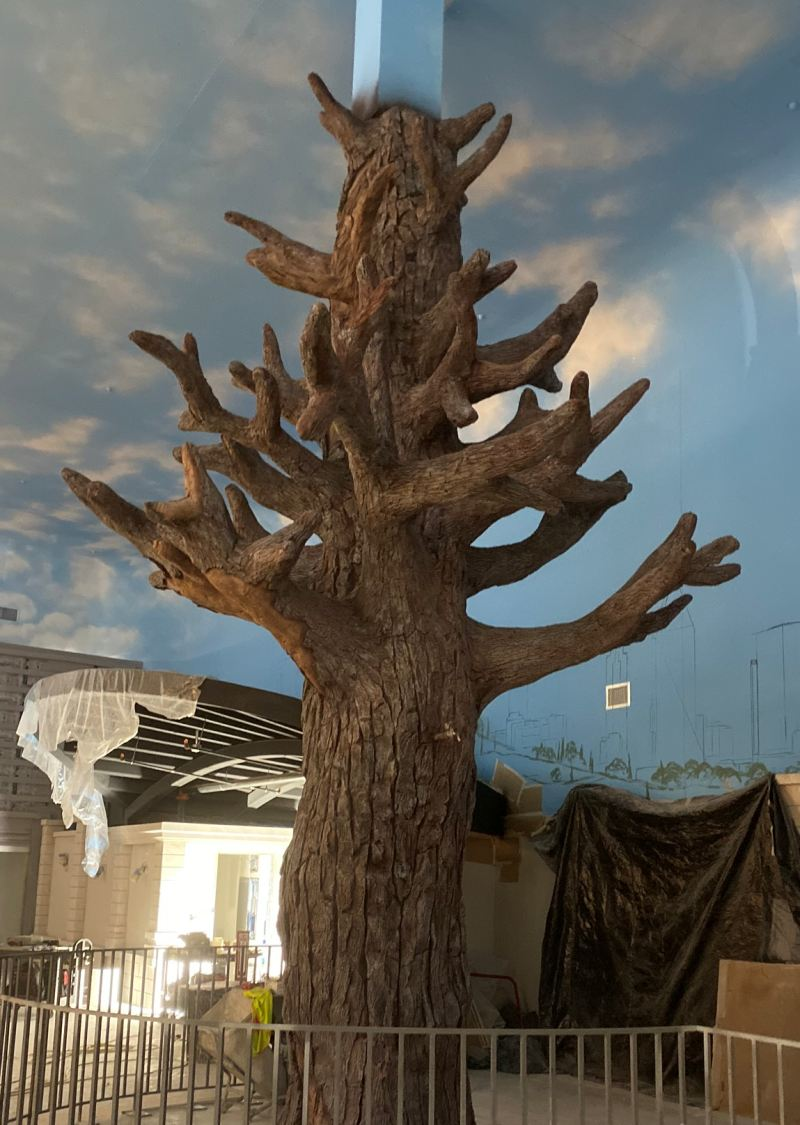 A faux tree made out of concrete spans to the ceiling of the KidZania space.