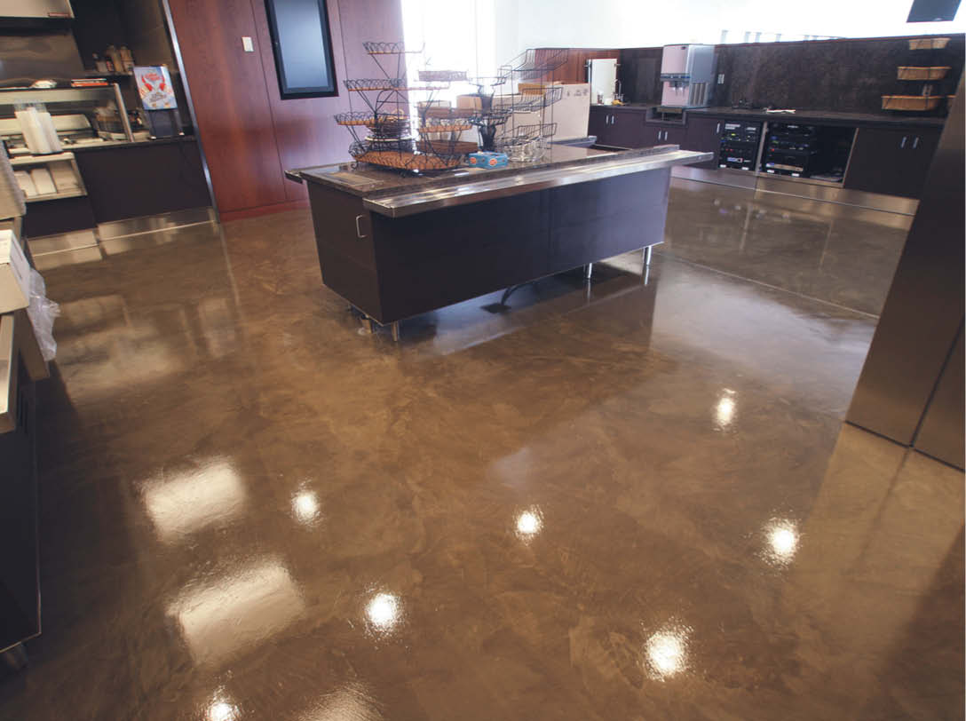 Brown concrete stained floors with a concrete countertop on an island in the middle.