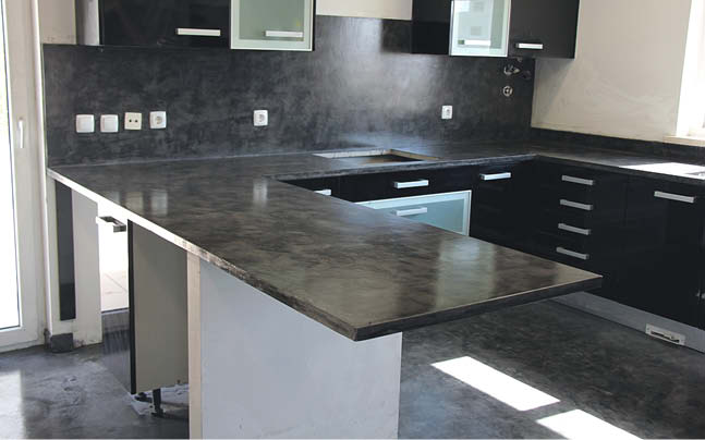 Dark concrete countertops in a kitchen with clean simple lines.