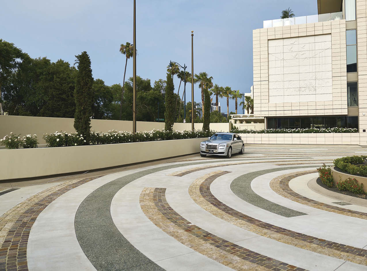 A car on a driveway in front of a hotel with circular stained design.