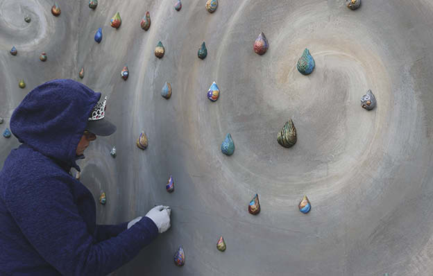 Applying the raindrops to the wall to achieve its desired design.
