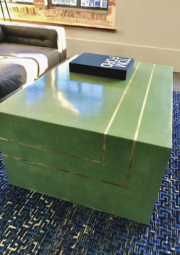 Green concrete table with gold lines.