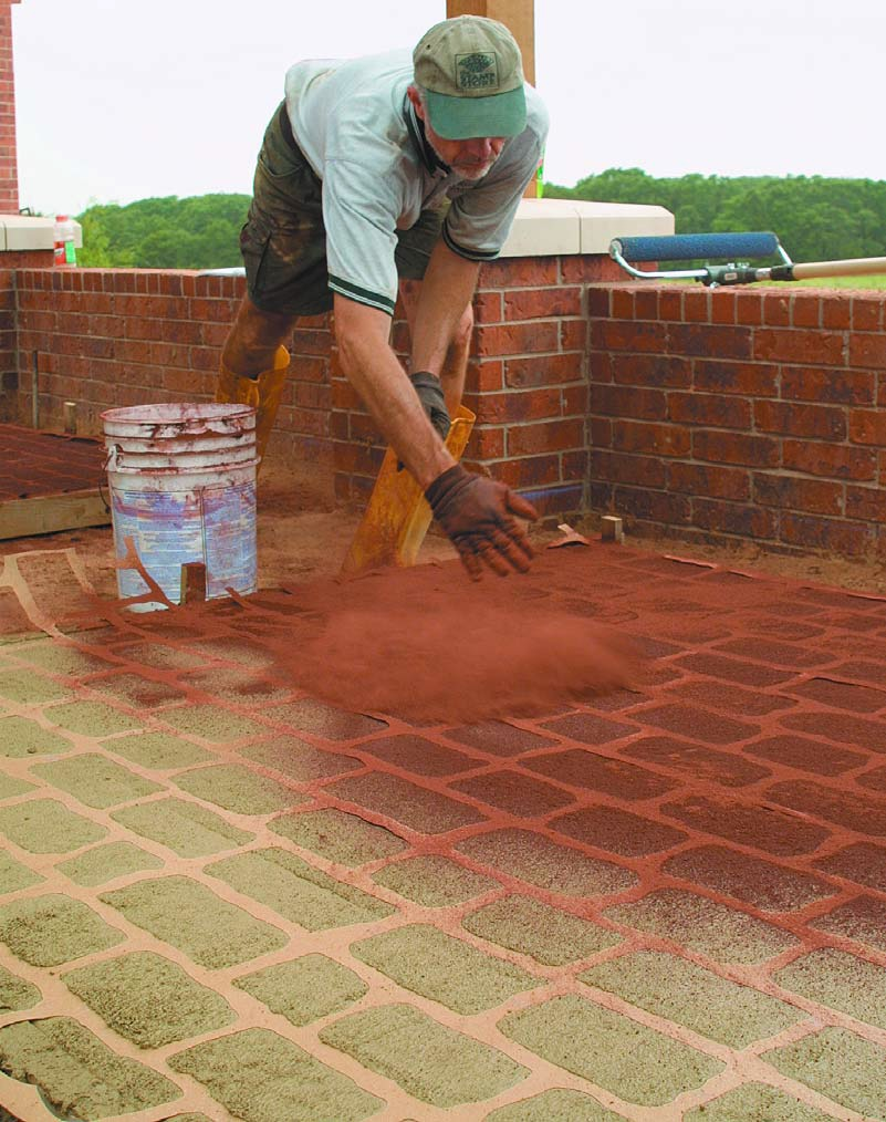 Doug Bannister applies the color to a stenciled concrete job.
