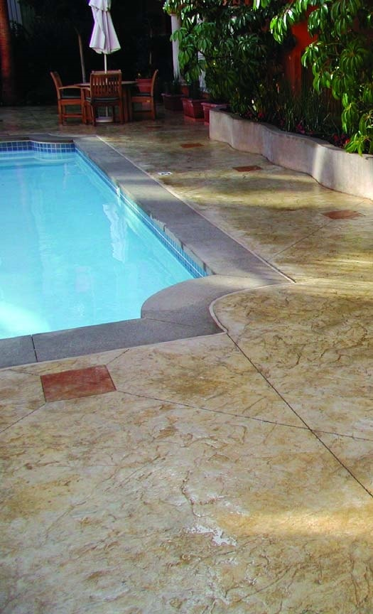 Swimming pool deck with control joints in the slab that have been camouflaged using red stain and a textured surfaced concrete.