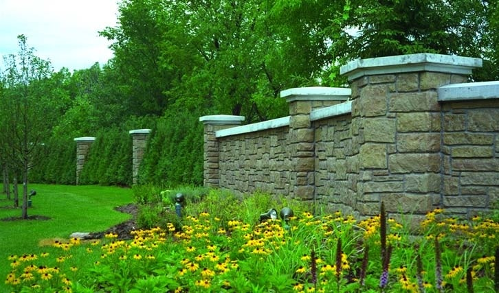 Tranquil garden with black eyed susans flowers protected by a concrete wall that looks like stone from the use of form liners.