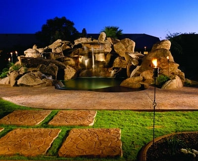 A stamped concrete patio is framed by water cascading down a concrete waterfall. The backlit water spills into a hot tub bordered by a stamped concrete patio and concrete rock formations.