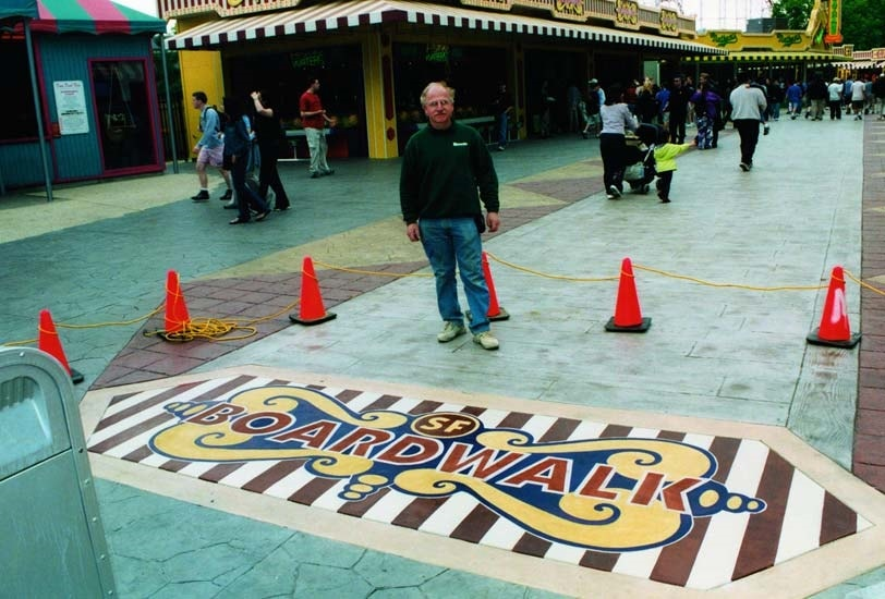 Bomanite contractor Ira Goldberg proudly stands in front of San Francisco boardwalk logo made with Bomanite materials.