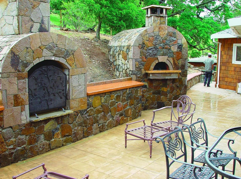 Outdoor living space is brightened up with stamped concrete and a faux stone stove.