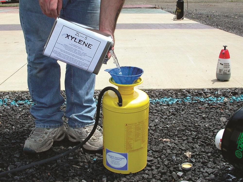 pouring xylene into a pump sprayer