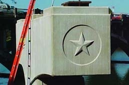 Bridge support beam made from concrete with a star inside a circle made using a form liner during the concrete pour.
