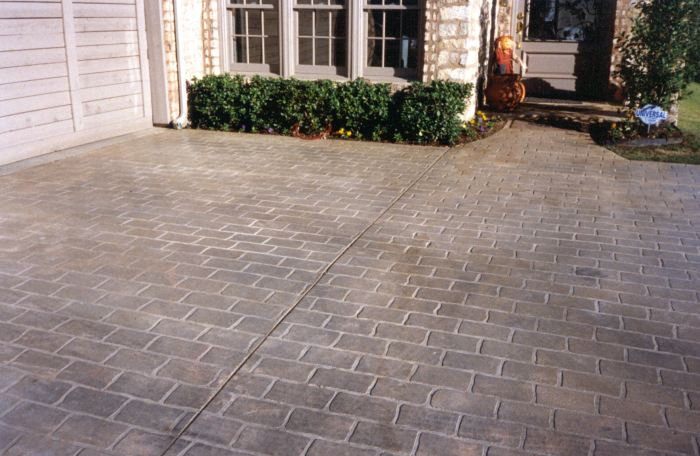 Concrete driveway that has been stenciled and colored to look like natural brick.