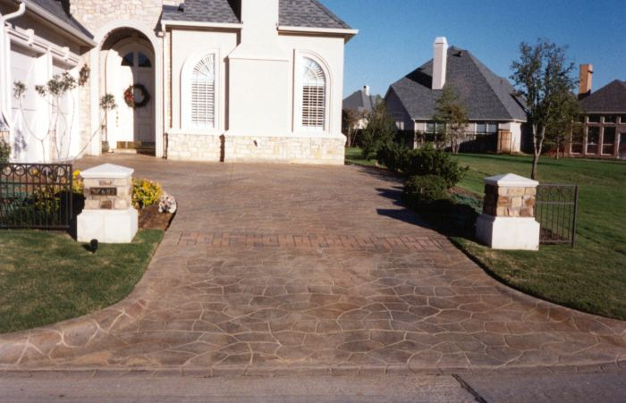 This concrete driveway was stenciled with a pattern that makes it look like it is inlayed brick that was done piece by piece.