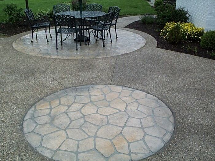 Embedded circular stencils create delineated areas on this large outdoor patio.