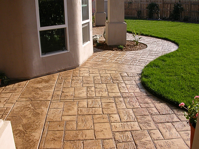 Stamped and colored concrete patio in browns with a rolling edge next to the bright green grass.