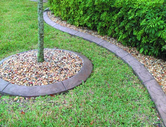 Decoratve concrete curbing around a flower bed gives a clean easy maintenance look.