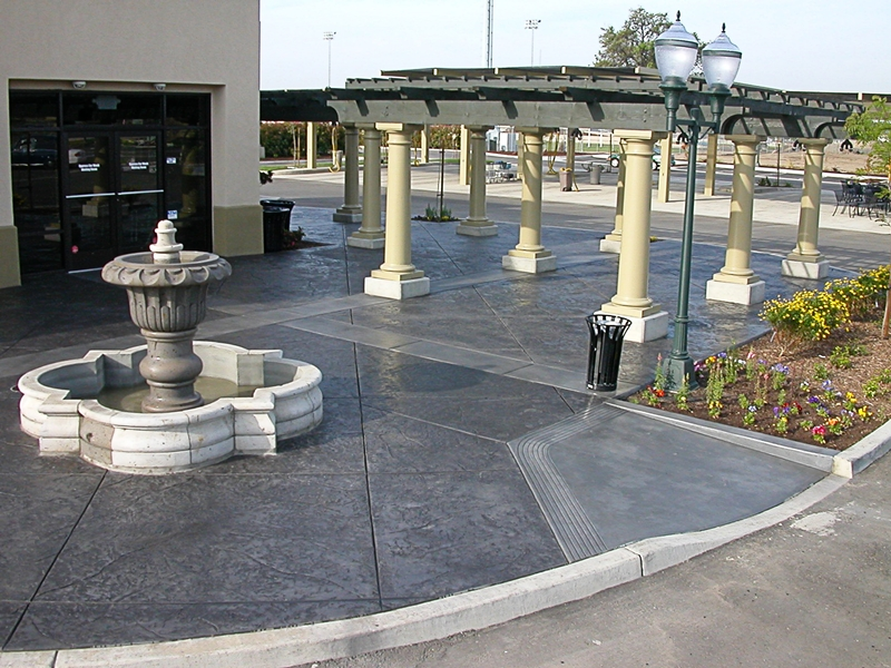 A water fountain and a pergola sit atop this charcoal gray stamped concrete patio.