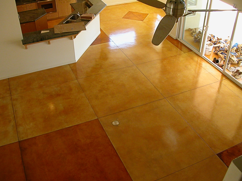 An overhead shot of stained concrete in orange and red colors.