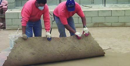 Two concrete contractors remove a texture skin from a concrete slab.