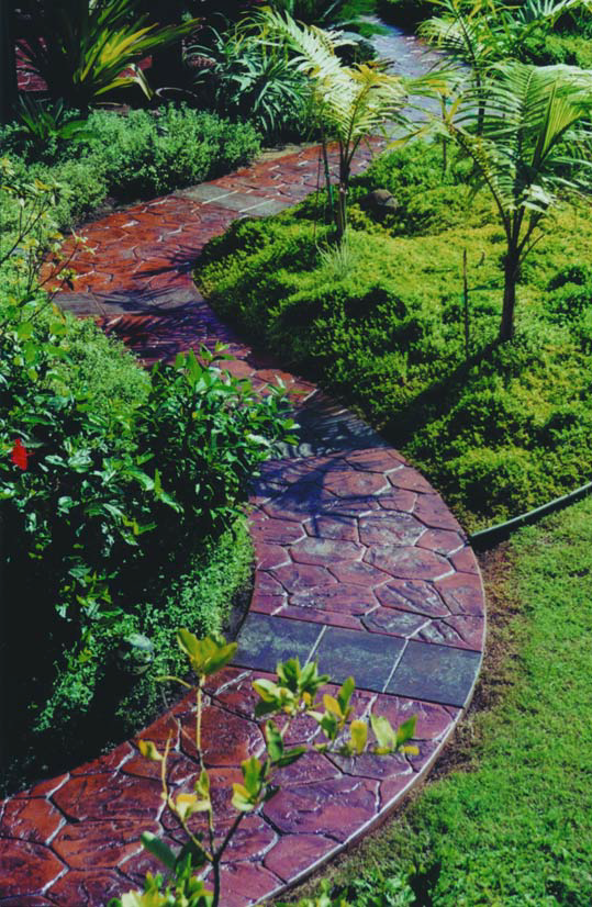 A winding concrete path that meanders through a garden is colored and stamped.