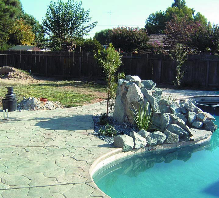 Pool deck rock feature and stamped concrete pool deck.