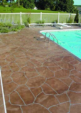 A finished swimming pool deck that has been stenciled and stained to look and feel like real stone.