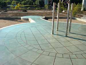 Beautiful light colored concrete patio in a tile like pattern circling a four pillar statue.