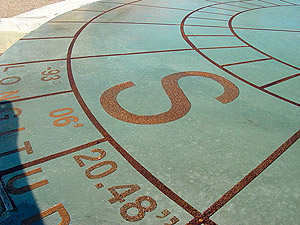 Stained and sealed concrete patio compass with directional degrees and direction indication