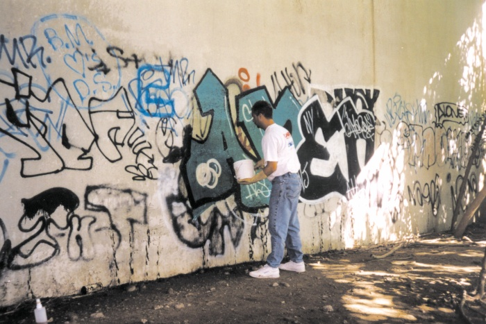 a man in front of a graffiti wall trying to clean it up