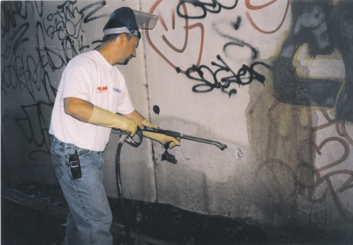 a person using a pressure washer as means of graffiti removal