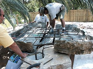 "building rocks around pool - A contractor installing a precast Rock & Water Creations piece starts by putting in a cinderblock wall with rebar, then placing the panels. ""We use a standard concrete mix with mesh in between panels,"" Reinwald says. ""The embossers get the mesh to match."""