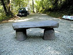 Faux rock bench made of concrete, sits at the entrance to a nature trail