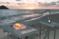 Outdoor concrete kitchen modeling on a beach in Hawaii during sunset.