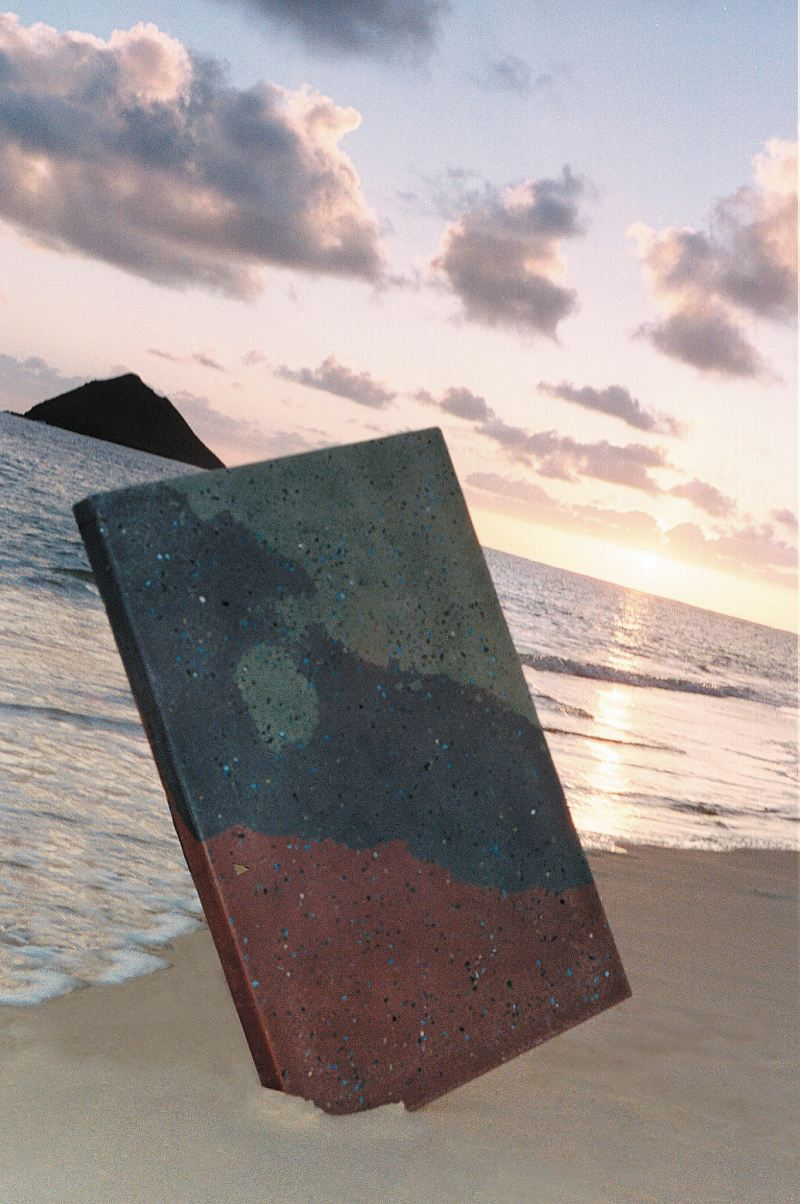 Rectangle slab of concrete that has been precast in three layered look standing up in the sand for this photo op.