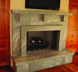 Concrete interior fireplace surround and mantel in a burnished faux finish texture.