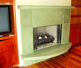 Celadon green colored concrete fireplace surround sits up off the hardwood floor in this living room.