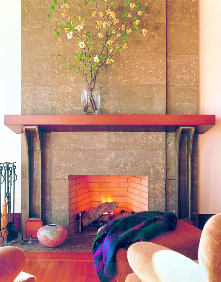 Fireplace mantle made of concrete enhances the tile look concrete behind.