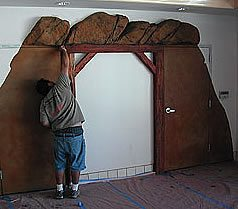 Final staining touches to a vertically carved concrete mine shaft entranced in a mini market in Southern California.