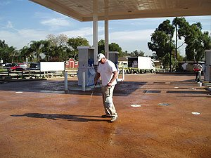 Richard Smith cleaning a large stained concrete gas station parking lot after his job was finished.