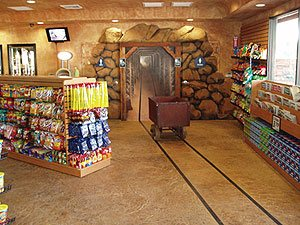 Mine shaft entrance in a mini market in southern California features stained and vertically carved concrete boulders.