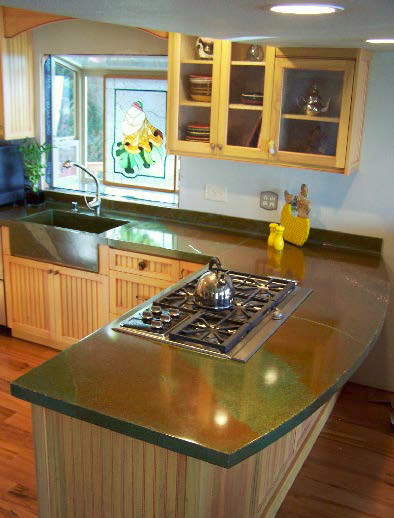 Green and orange concrete countertop gives kitchen a clean and modern look