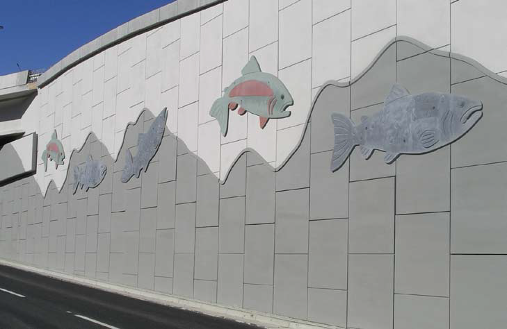 Large lightweight fish are placed on the side of this freeway to change the drab gray concrete wall into art for drivers.