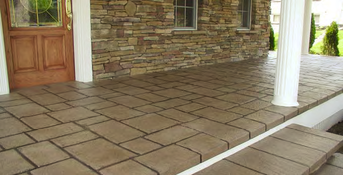 A decorative concrete patio that includes a step has been stamped and stained to look like natural stone.