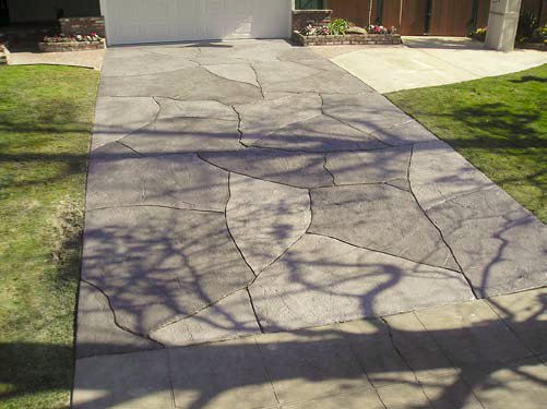 This concrete driveway has been made over to look like stone perfectly placed and stained.