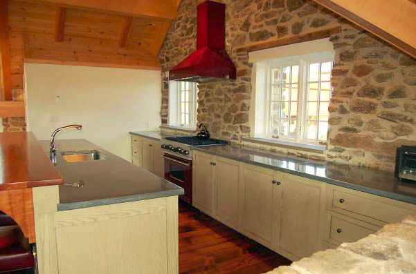 A look at a concrete countertop in a kitchen with a rock wall backsplash.