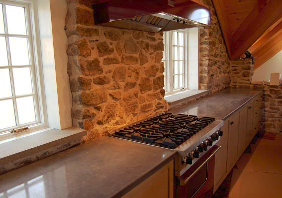 Kitchen with a rustic rock-like backsplash and concrete countertops.